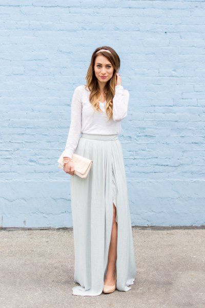 Long-sleeved floor-length dress with a gathered waist and a white clutch