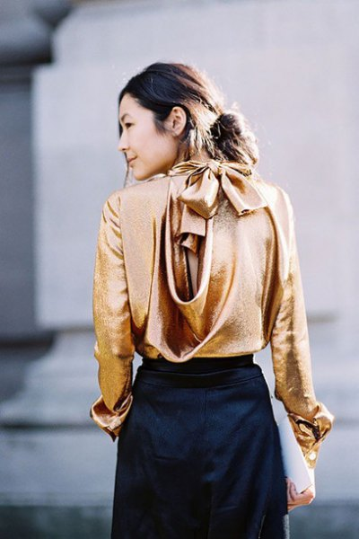 Metallic blouse with gold waterfall neckline and black mini skirt