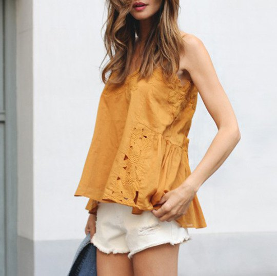 Sleeveless blouse made of gold lace with white mini-shorts