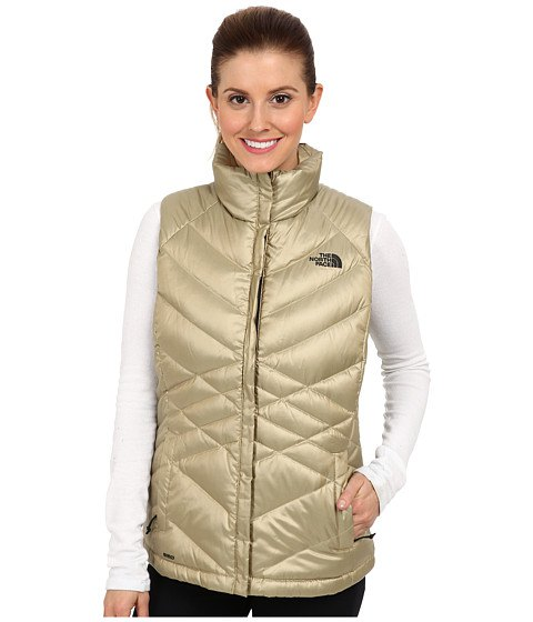 golden down vest with white long-sleeved T-shirt and black jeans