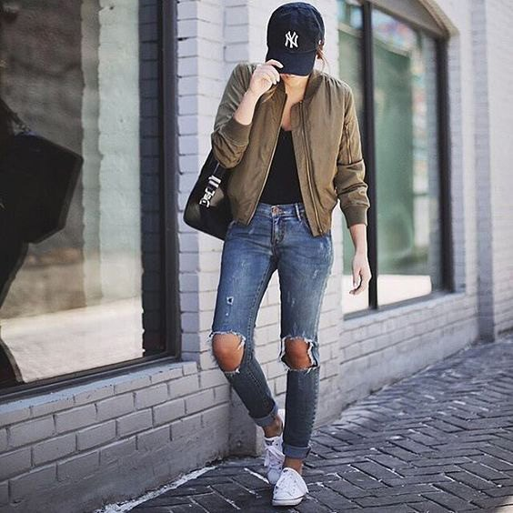 Green bomber jacket with a black top with a scoop neckline and heavily ripped jeans