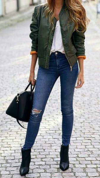 green bomber jacket with blue ripped skinny jeans