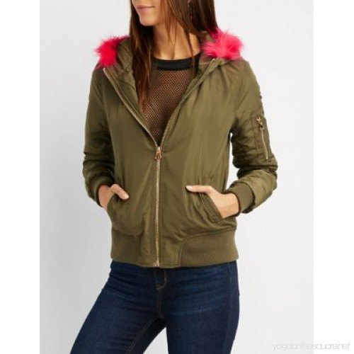 green bomber jacket with fishnet blouse and blue jeans
