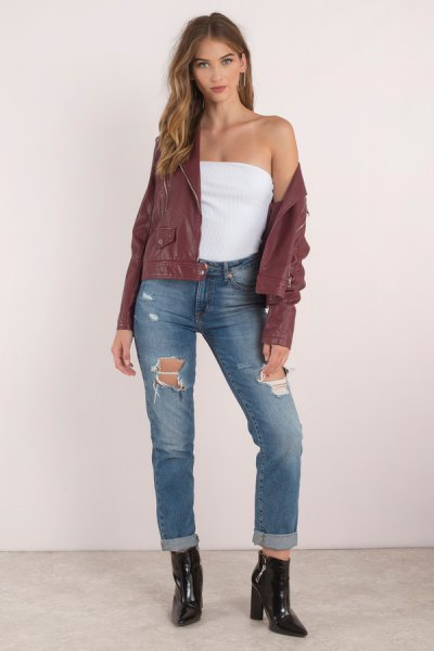green bomber jacket with a tube top and ripped jeans with cuffs