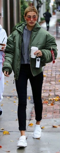 green bubble coat with gray hoodie and black jeans