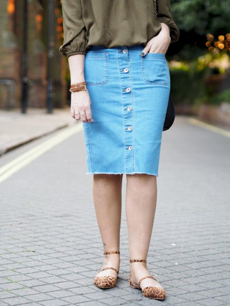 green buttonless blouse with a knee-length skirt with blue denim button on the front
