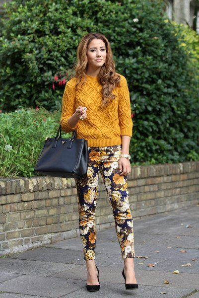 green cable knit sweater with black floral trousers