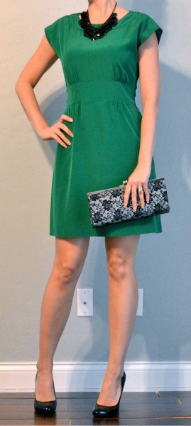 green mini cocktail dress with cap sleeves and black statement chain