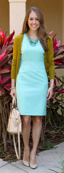 Green cardigan with a light blue, knee-length dress with a ruffled waist