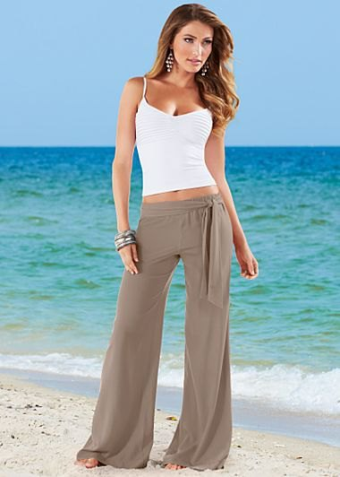 green flared cotton beach pants with white, short-cut vest top