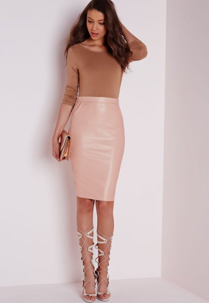 Green figure-hugging sweater with a high-waisted, knee-length leather skirt made of light pink leather