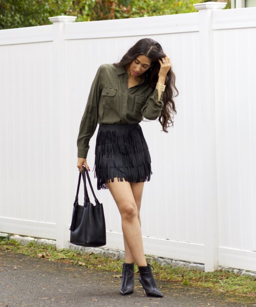 green shirt with button front and black mini skirt and boots