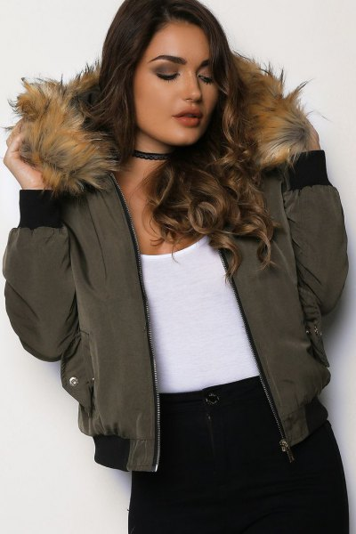 Bomber jacket with a green fur hood, white tank top and black collar