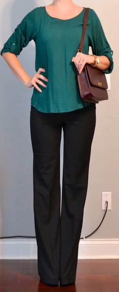 green blouse with round sleeves and scoop neckline and black chinos with straight legs