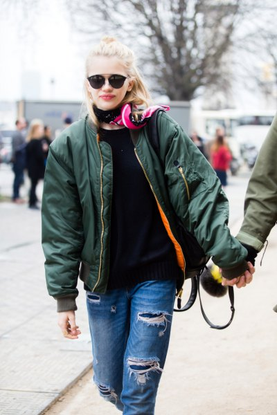 green hooded jacket with blue destroyed jeans