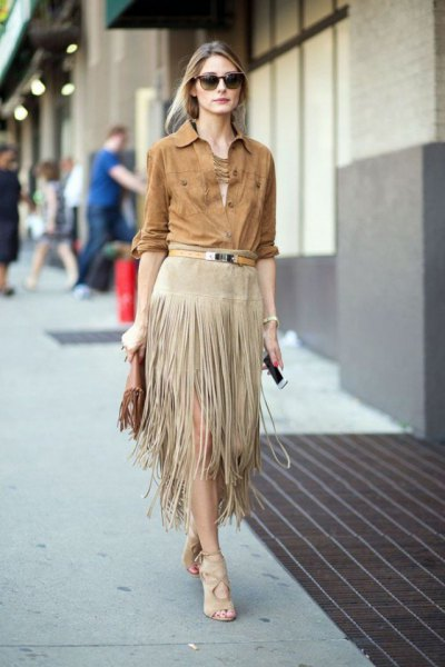 green long-sleeved suede shirt with buttons and light gray midi skirt with fringes