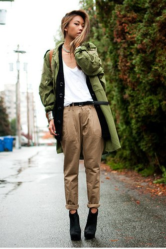green longline military jacket with white tank top and chinos with cuffs