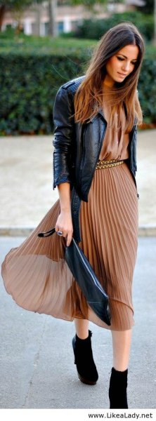 green midi dress made of pleated chiffon with black leather jacket