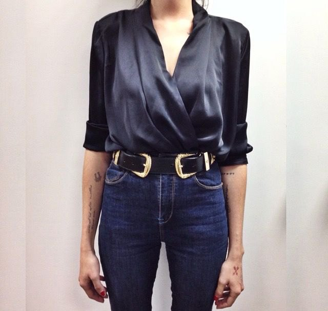 Green satin blouse with V-neck and blue jeans