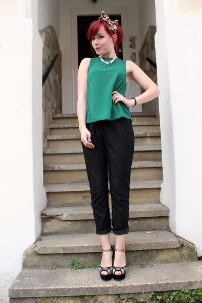 green sleeveless top with black trousers with cuffs