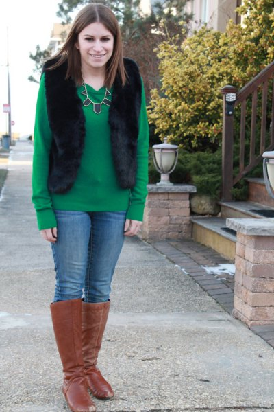 green sweater with black vest and knee-high boots made of camel suede