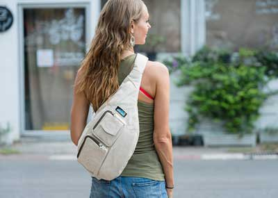 green tank top with ivory-colored shoulder bag and light blue jeans