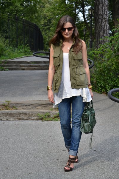 green utility vest with white sleeveless tunic top and blue jeans with cuffs