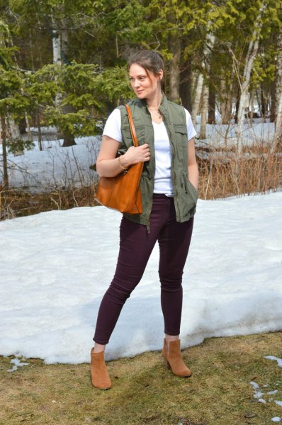 Green utility waistcoat with a white T-shirt and black jeans with a slim fit