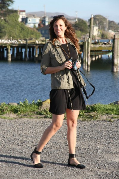 green windbreaker with black mini dress and ballerinas with ankle straps
