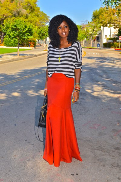 gray-black striped long-sleeved top with boat neckline and orange maxi skirt