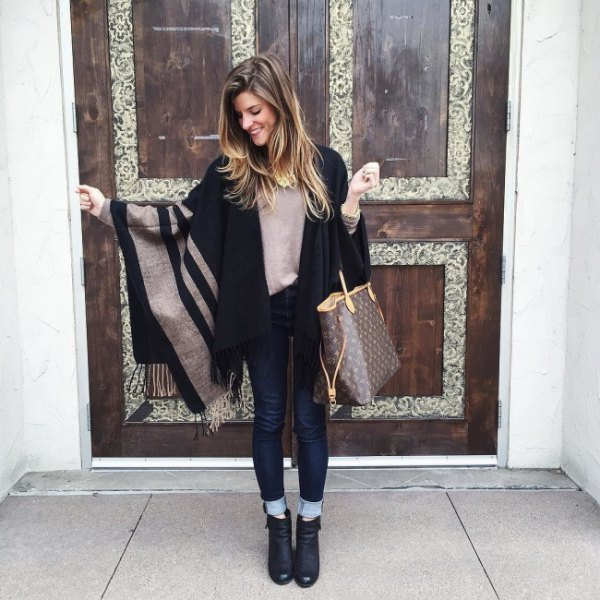 gray-black striped cape with dark blue skinny jeans with cuffs