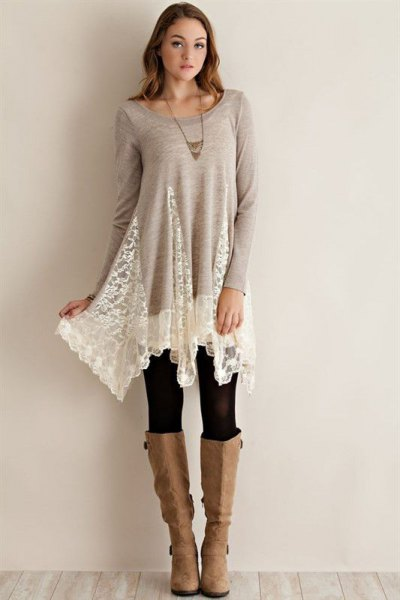 long tunic top made of gray and white lace with black leggings and knee-high boots