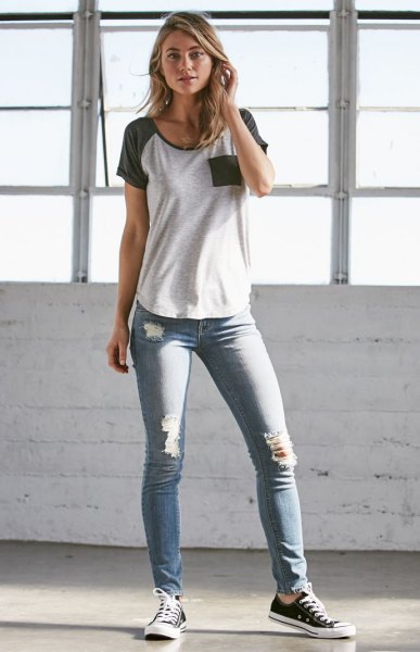 gray and white t-shirt with gray skinny jeans with a low waist