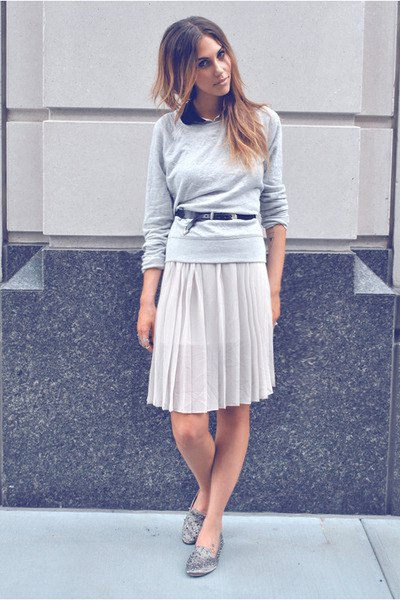 gray sweater with relaxed fit and knee-length pleated skirt and silver slippers with spikes