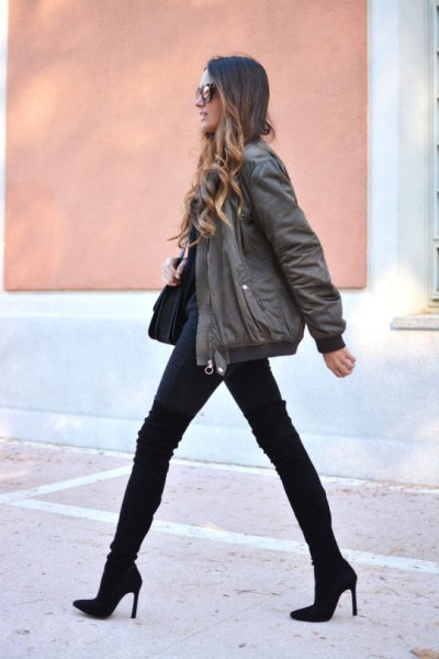 gray bomber jacket with black jeans and boots in the middle of the calf