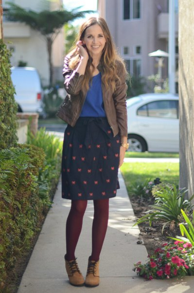 gray bomber jacket with royal blue t-shirt and knee-length skirt