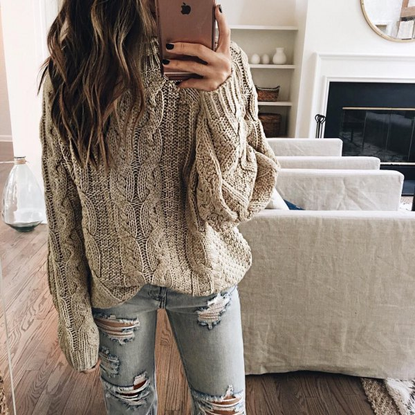 gray cable knit sweater with ripped light blue skinny jeans