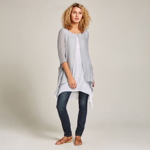 gray cardigan with a long white top and dark jeans