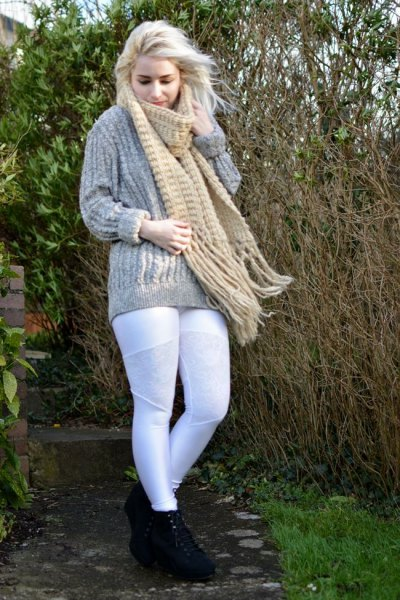 gray, coarse-grained knitted sweater with a blushing fringed scarf