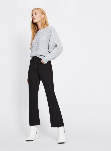 gray, coarsely knitted sweater with black, flared button fly jeans