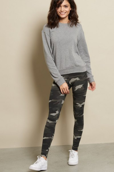 gray, chunky sweater with camouflage gaiters and white sneakers