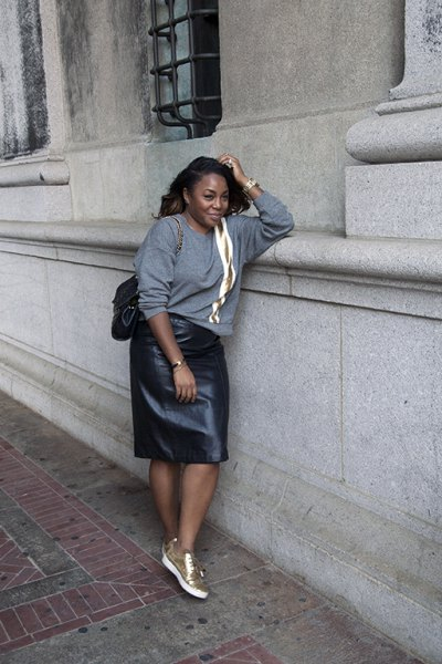 gray, chunky sweater with leather skirt and white and gold sneakers