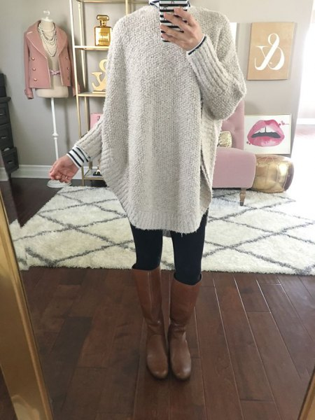 gray, chunky sweater with a striped T-shirt and knee-high leather boots