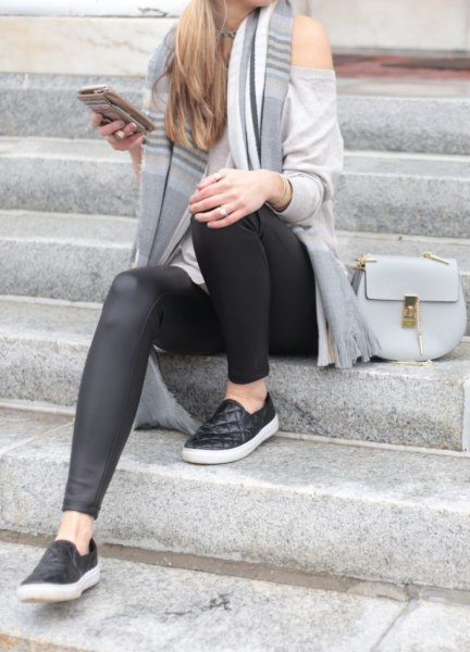 gray slouchy sweater with cold shoulder and striped, long knitted scarf