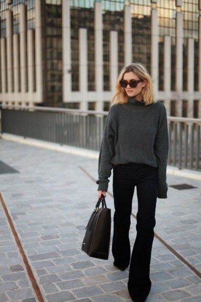 gray, thick sweater with a round neckline and black, flared jeans