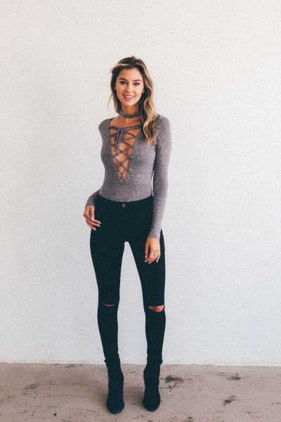 gray criss-cross top with deep V-neck and torn jeans