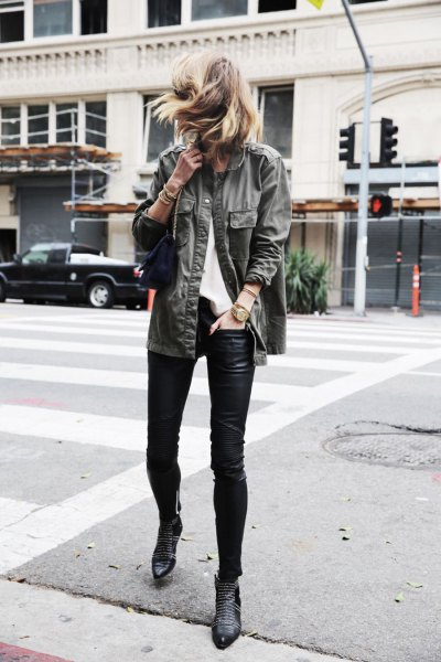 gray denim jacket with black leather gaiters and boots with ankle spikes