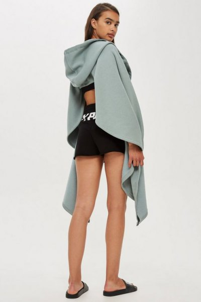 gray draped hoodie with cut out back and black mini running shorts