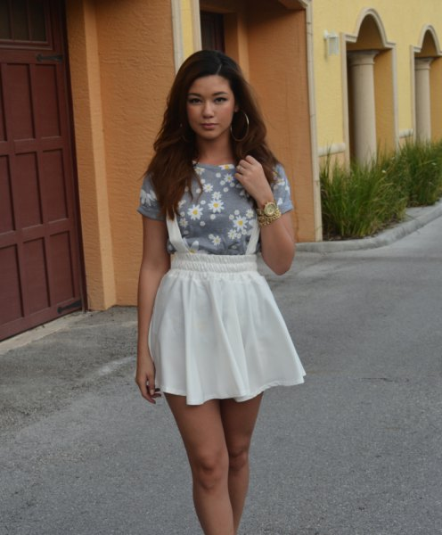 gray t-shirt with floral pattern and white mini skater suspender skirt