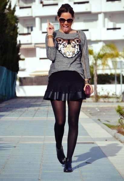 gray graphic sweater with black, flared miniskirt and short boots